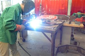 Student welding a piece of metal for a project